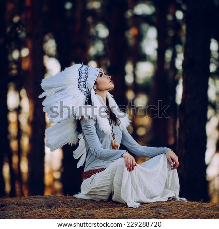 Artistic portrait of young beautiful woman in Indian headdress. Shallow depth of field - stock photo