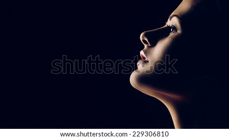 Artistic portrait of young beautiful woman on black. Copy space on left