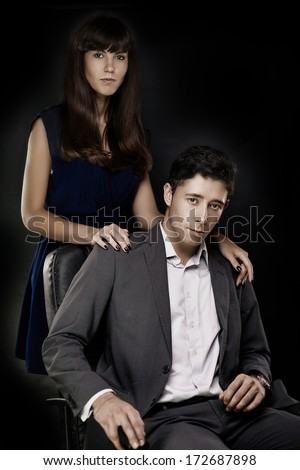 Artistic portrait of young elegant couple on black