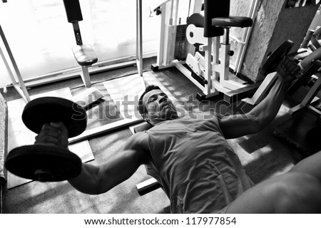 artistic shot, black and white, of a young bodybuilder hard training in the gym: incline dumbbell press - stock photo