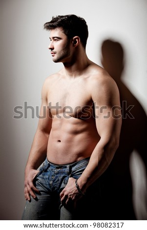 artistic shot of a handsome young man propped on the wall