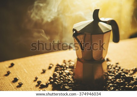 Artistic shot of old coffee maker and coffee beans, shot on canvas background  - stock photo