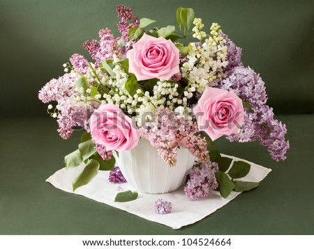 Artistic still life with huge bouquet of lilac and lily of valley flowers and roses on painting background - stock photo