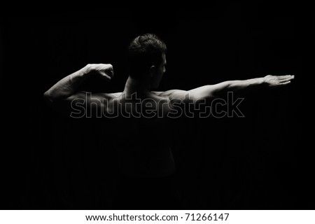Artistic strong man on black background, low key lighting style