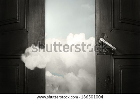 Artistic surreal background representing an opened door with the sky and a cloud that enters - stock photo