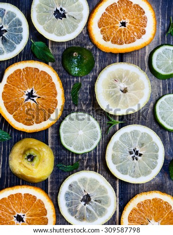Artistic top view photo of different citruses - lemon, lime, orange - on rustic wooden background. Slices ripe fruits. - stock photo