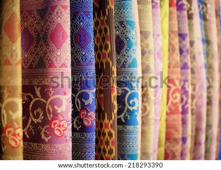 artistic variety shade tone colors ornaments patterns of thai silk textiles with traditional cultural decoration ornaments design by village people hanging in a street market in KHONKAEN, THAILAND  - stock photo