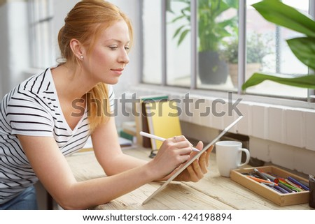 Artistic young designer working on the office at her desk in front of the window drawing on a tablet computer