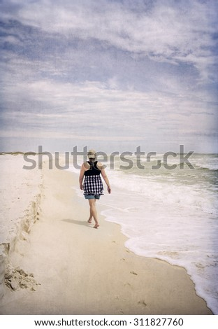 Artistically textured and toned photograph of an active mature woman viewed walking away from the camera on a beautiful sunny beach. - stock photo