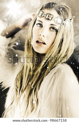 Artistically toned image in cool tones of a beautiful blonde woman in white with a jewelled headband standing under falling snowflakes during winter in a enchanting snow princess concept