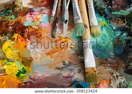 artists brushes and oil paints on wooden palette. macro artist's palette, texture mixed oil paints in different colors and saturation. palette with paintbrush and palette-knife - stock photo
