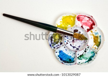 Artists flower shaped style watercolour palette and brush on a white textured paper background with copy space