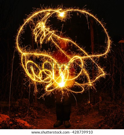 Artists juggling with two burning poi's at fire performance. Long exposure causing painting with light - stock photo