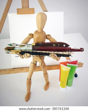 artists mannequin standing in front of blank canvas holding paint brushes with tubes of paint on desk. - stock photo