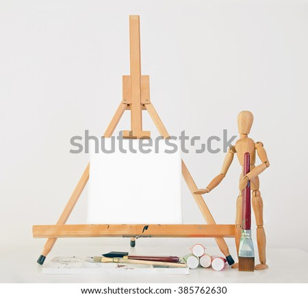 artists mannequin standing next to blank canvas on easel with copy space holding a paint brush. Paint tubes and pallet on desk. - stock photo