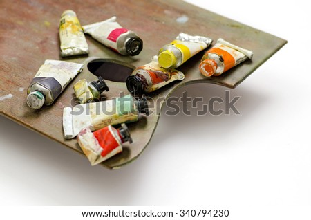 Artists paint tubes on palette; used tubes of oil paints resting on artist palette, isolated on white ground; differential focus  - stock photo