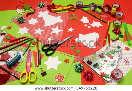 Arts and craft supplies for Christmas. Red and green color paper, pencils, different washi tapes, craft scissors, cardboard bell cut and decorations.