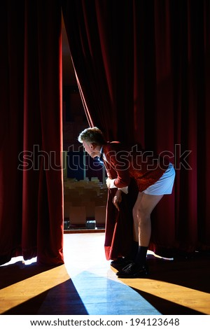 Arts and entertainment in theatre with funny man working as anchorman, standing with pants behind the scenes and looking at pit - stock photo