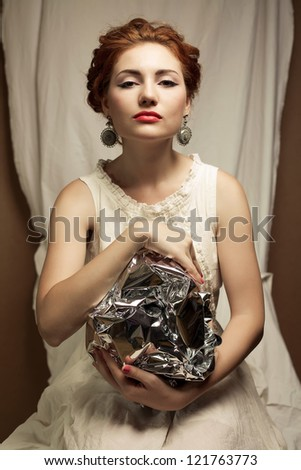Arty portrait of a fashionable queen-like ginger model holding silver foil sphere over white curtain background. Studio shot