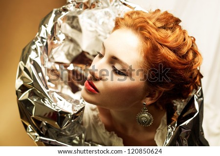 Arty portrait of a fashionable queen-like ginger model with silver foil cape over white curtain background. Close up. Studio shot - stock photo