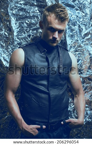 Arty portrait of muscular young and handsome man with muscular hands and trendy haircut with intense look in sleeveless vest of dark jeans posing over silver foil background. Close up. Studio shot - stock photo