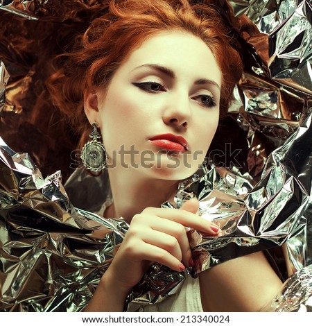 Arty portrait of sad fashionable queen-like red-haired (ginger) model with silver foil cape. Silver vintage earrings. Perfect make-up. Retro style. Close up. Studio shot - stock photo