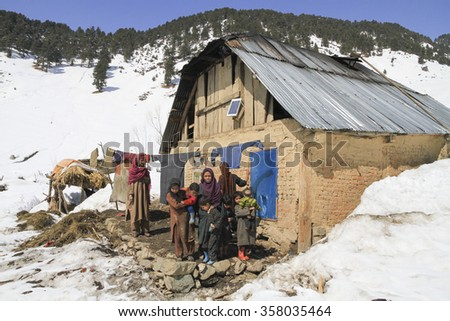 ARU KASHMIR CIRCA FEBRUARY 2012 - Unidentified Kashmiri Nomadic family standing on the balcony of their wooden hut catching some midwinter sun and drying washing.
