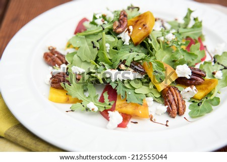 Arugula and Beet Salad with Goat Cheese and Candied Nuts - stock photo