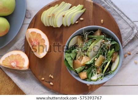 ARUGULA, FRESH PEAR, GRAPEFRUIT AND PAIN NUTS SALAD IN A BOWL