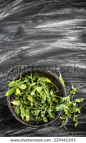 arugula in an old metal plate on black table
