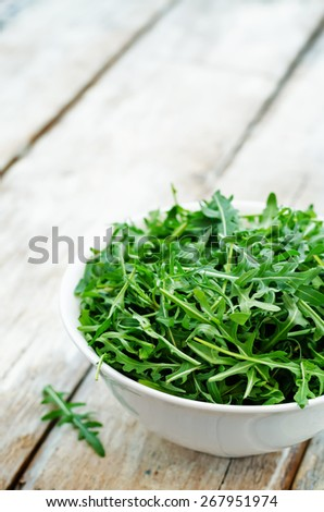 arugula on a white wood background. toning. selective focus