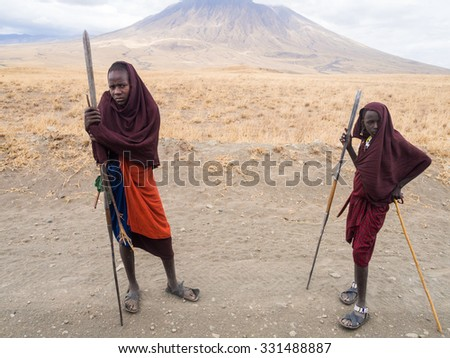 ARUSHA REGION, TANZANIA - OCTOBER 16, 2015: Two young Maasai warriors on the road to Lake Natron. Ol Doinyo Lengai (Mountain of God in the Maasai language) in the background