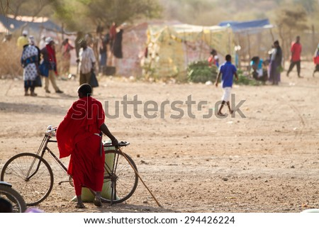 ARUSHA, TANZANIA - AUGUST 18: Masai man with bycicle, masai people still live in the old way but with a slight use of technology august 18, 2014 in Arusha, Tanzania - stock photo
