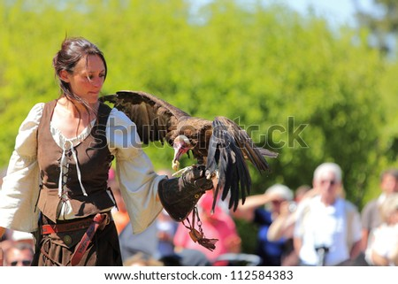 ARVILLE,FRANCE, AY 23: A female bird tamer with an eagle during a show on May 23 2010 in Arville,France.There was a Medieval market in the gardens of a well preserved Templars Commanderie in France.