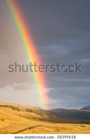 As a rain storm passes, the setting sun creates a vibrant rainbow in Lamar Valley, Yellowstone Park, Wyoming - stock photo