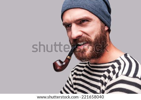 As rough as he is. Serious young bearded man in striped clothing smoking a pipe and looking away while standing against grey background