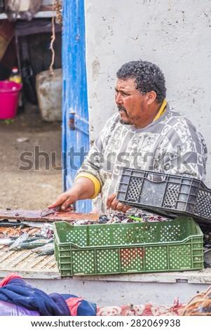 AS-SAWIRA, MOROCCO, APRIL 7, 2015:  Fishermen clean fish in port of As-Sawira - stock photo