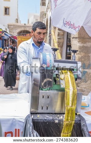 AS-SAWIRA, MOROCCO, APRIL 7, 2015: seller of sugar cane juice squeezes it for selling - stock photo