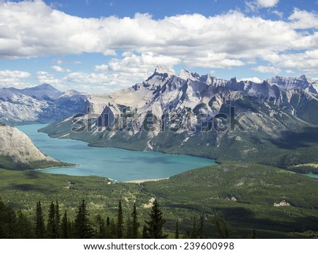 As seen from the top of the C Level Cirque trail, Lake Minnewanka in the Banff National Park in the Canadian Rocky Mountains glows with a soft blue color as light reflects from glacial flour and silt. - stock photo