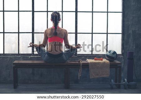 As the city bustles below, this fit, athletic woman sits quietly meditating in lotus position on a wooden bench. - stock photo