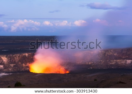 As the sun sets Kilauea volcano begins to show the hot lava glow of its active vent, spewing out smoke as the molten rock burns. - stock photo