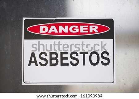 Asbestos danger warning sign on glass window at old rusty toxic contaminated building. - stock photo