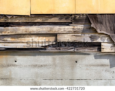 Asbestos siding falling apart with exposed wood and felt underneath.  - stock photo