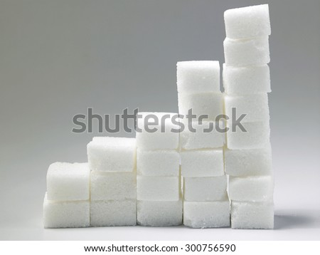 Ascending stacks of sugar cubes over gray background. This in a concept for high risk of diabetes or other diseases caused by excessive consumption of sugar - stock photo