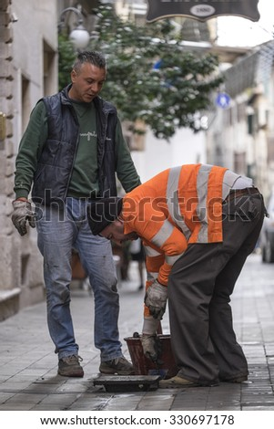 ASCOLI PICENA, ITALY - OCTOBER 5 2015 - Two workers open an unsecured sewer manhole in a street of the city of Ascoli Picena, Italy - stock photo