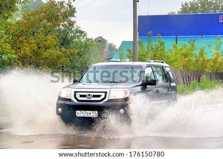 ASHA, RUSSIA - SEPTEMBER 7, 2013: Black Honda Pilot car at the city street during a strong flood. - stock photo