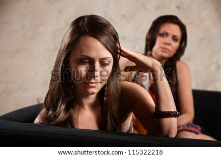 Ashamed woman with hand on head looking away from friend - stock photo