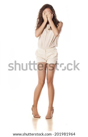 ashamed young girl holding hands on her face - stock photo