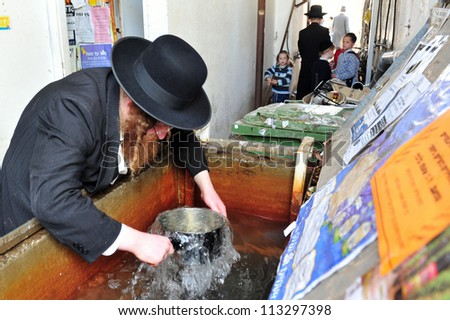 ASHDOD - APRIL 15: Ultra Orthodox Jewish men repare for the Jewish holiday of Passover on April 15 2011 in Ashdod, Israel. - stock photo