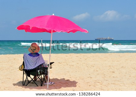ASHDOD ,ISR - 23 JULY 2011:Israeli woman sit under beach umbrella in Ashdod Arches Beach. Ashdod is the sixth largest city in Israel with population of over 200,000 people.